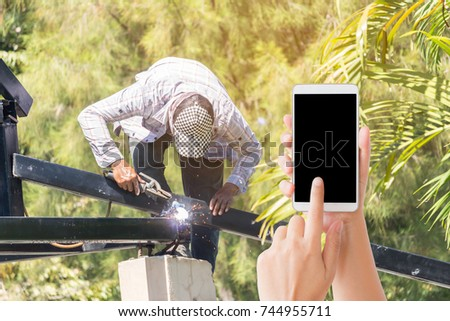 woman use mobile phone and the worker that is welding on the roof #744955711