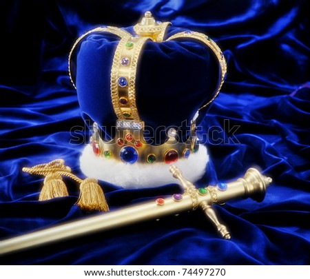 Beautiful crown and sword on royal blue fabric with soft window light and copy space