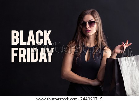 Elegant brunette woman wears sunglasses and black dress holding black shopping bags, black friday concept
