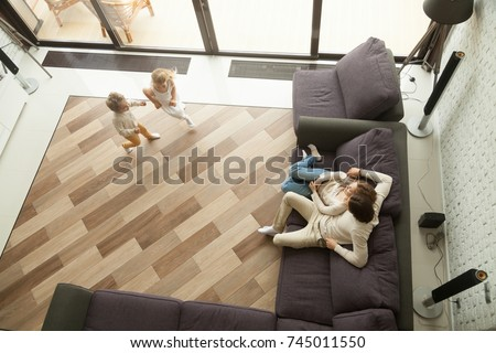 Kids playing little boy and girl running in cozy living room interior while parents relaxing on comfortable sofa at home, happy family leisure activities in big house apartment with terrace, top view #745011550