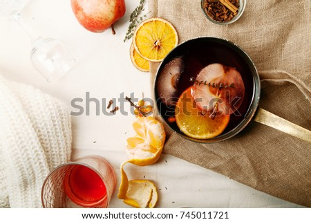 Mulled wine in copper saucepan cooked with slices of orange, apple and thyme. Top view. Linen cloth and tangerines on the table. Scandinavian winter concept. Horizontal composition with copy space. #745011721