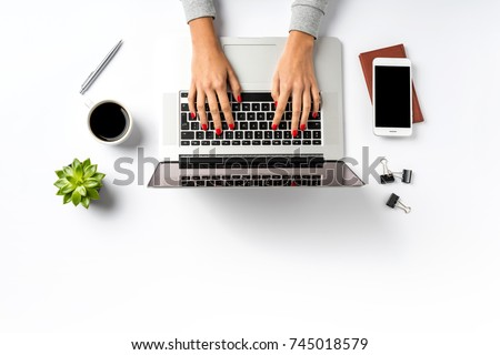 Female hands working on modern laptop. Office desktop on white background Royalty-Free Stock Photo #745018579