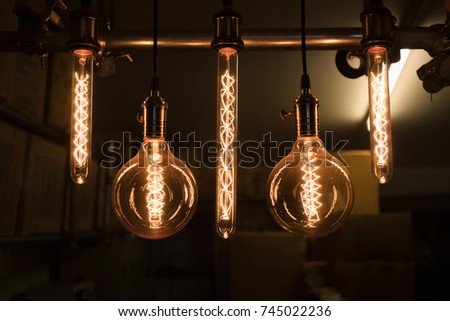 Close up group of hanging light bulbs with storage room background in darkness. Retro style #745022236
