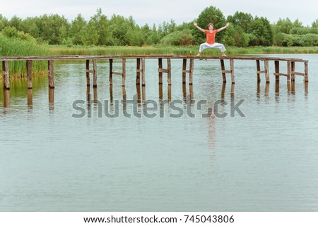 A man doing yoga on wooden pier at the lake #745043806