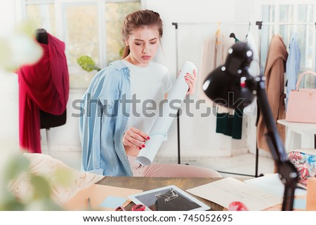 Fashion designers working in studio sitting on the desk #745052695