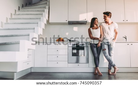 Full-length image of romantic couple at home. Attractive young woman and handsome man are enjoying spending time together while standing on light modern kitchen. #745090357