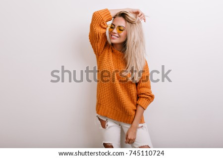 Indoor portrait of glad fair-haired girl wearing ripped jeans and round yellow glasses. Smiling blonde woman in stylish knitted cardigan posing with eyes closed and hand up. #745110724