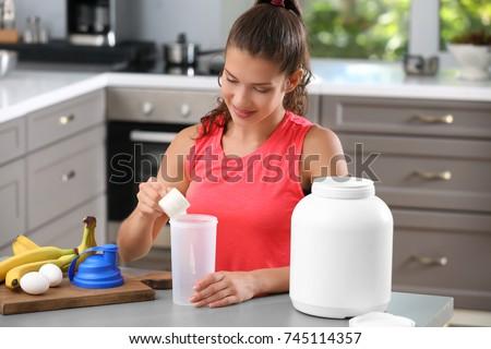 Woman preparing protein shake in kitchen #745114357