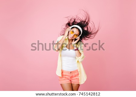 Glad latin girl in colorful clothes posing with black hair waving and laughing. Pleased asian female model in headphones having fun in summer studio photoshoot.