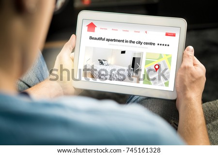 Man search apartments and houses online with mobile device. Holiday home rental or real estate website or application. Imaginary internet marketplace for vacation lodging or finding new home. #745161328
