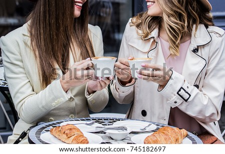 Having good time with best friend. Cropped image of two cheerful beautiful women looking at each other and keeping cups of coffee in their hands while sitting in french cafe. Women drinking coffee.