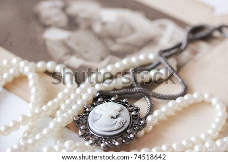 victorian cameo and pearl necklace in front of vintage picture