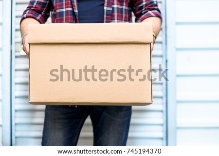 Young man holding a moving cardboard box in front of a storage door.Life style, storage, moving, storing, organizing concept. Space to write #745194370