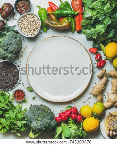 Clean eating healthy cooking ingredients. Vegetables, beans, grains, greens, fruit, spices over grey marble background, white plate with copy space in center, top view. Diet food concept. Food frame #745209670