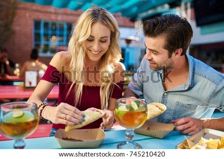 romantic couple eating street tacos at outdoor mexican restaurant