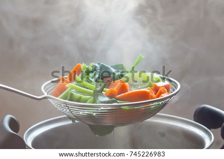 The steam from the vegetable colander in the darkSelective focus. Royalty-Free Stock Photo #745226983