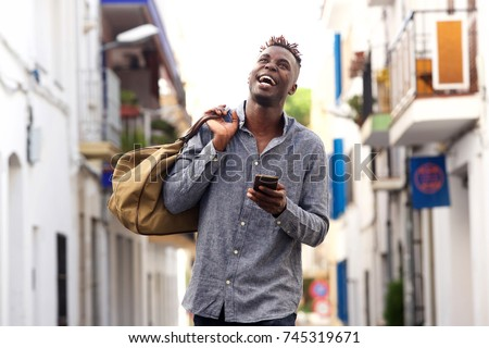 Portrait of cheerful young afro american guy holding handbag walking outside with mobile phone #745319671