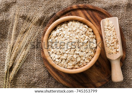 Rolled oats, organic oat flakes in wooden bowl and golden wheat ears on wooden background. Healthy lifestyle, healthy eating, vegan food concept #745353799