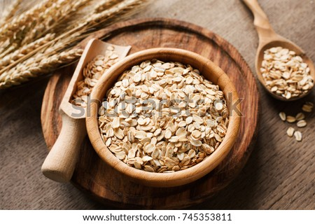 Rolled oats, organic oat flakes in wooden bowl and golden wheat ears on wooden background. Healthy lifestyle, healthy eating, vegan food concept #745353811