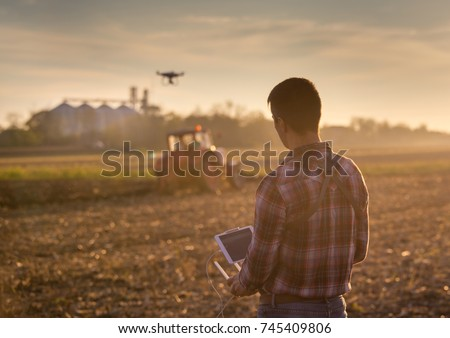 Attractive farmer navigating drone above farmland with silos and tractor in background. High technology innovations for increasing productivity in agriculture #745409806