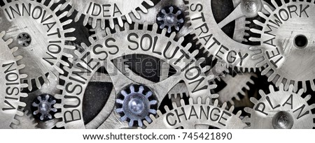 Macro photo of tooth wheel mechanism with BUSINESS SOLUTION, PLAN, STRATEGY, CHANGE, INNOVATION, VISION, TEAMWORK and IDEA words imprinted on metal surface Royalty-Free Stock Photo #745421890