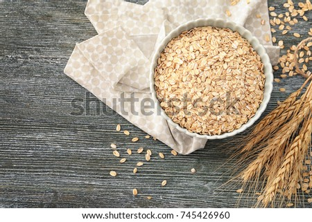 Bowl with oatmeal flakes on wooden background #745426960