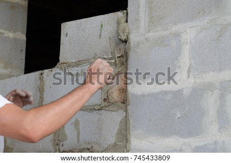 Migrant worker building cinder block wall in desert setting #745433809