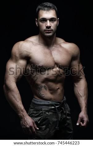 Handsome muscular male in front of black background #745446223