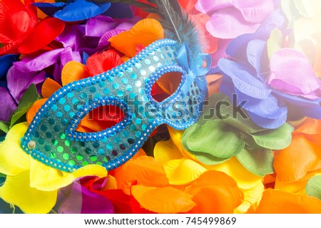 Sparkly blue carnival mask sits on bright background of rainbow colored flower leis in a celebratory pile