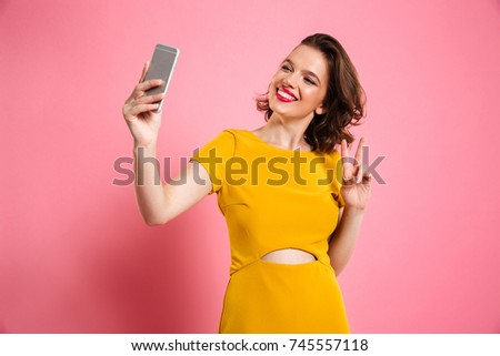 Cute pretty girl with bright makeup showing peace gesture while taking selfie on mobile phone, isolated over pink background #745557118