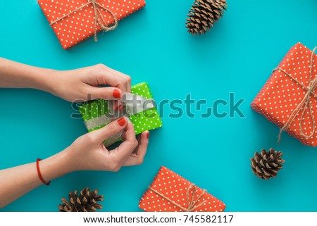 Christmas and New Year holiday composition with gift boxes, pine cone, women's hands pack a gift on the blue background. Top view, flat lay. Copyspace #745582117
