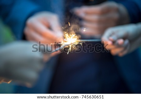 Blurry of hands with firework.Picture showing group of friends having fun with sparklers