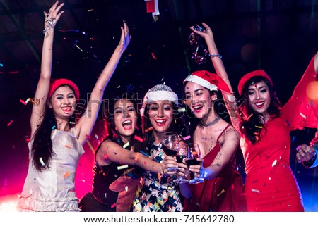 Group of happy young lady dancing together at nightclub with smoke and laser light. Friends celebrates new year together and disc jockey mixing music on background. #745642780