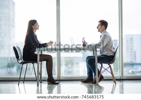 Businessman and woman having a discussion in the office face to face at table #745683175
