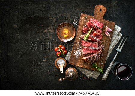 Sliced medium rare grilled beef ribeye steak on cutting board on dark background #745741405
