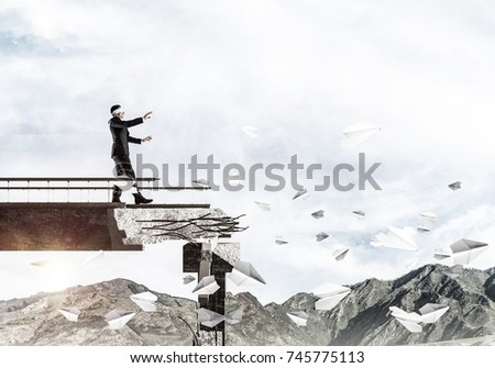Businessman walking blindfolded on concrete bridge with huge gap as symbol of hidden threats and risks. Skyscape and nature view on background. 3D rendering. #745775113