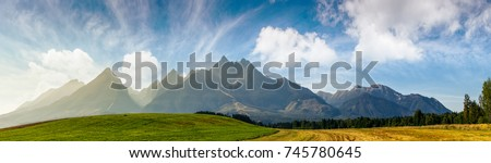 rural fields near Tatra Mountains in summer time. beautiful panorama of agricultural area. gorgeous mountain ridge with high rocky peaks #745780645