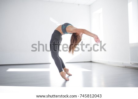 Young girl performing dance elements in the studio in front of a mirror. #745812043