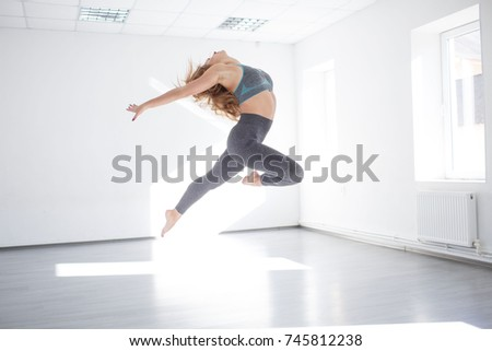 Young girl performing dance elements in the studio in front of a mirror. #745812238
