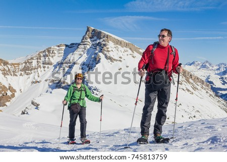 Senior couple is snowshoe hiking in alpine winter mountains. Bavaria, Germany. #745813759