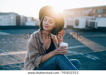 Portrait of beautiful young woman, in cute and adorable outfit, linen coat and fedora stylish fashion hat, drinks coffee from to go take away cup in amazing sunset light flares  #745832353