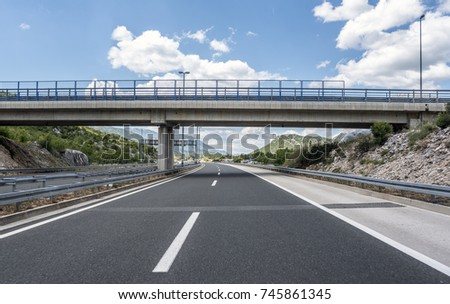 Bridge over a highway on a background of mountains and blue sky. #745861345