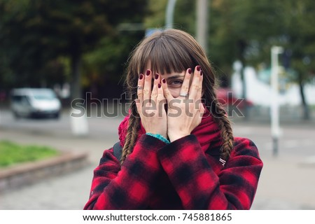 Young woman hides her face in her palms and spies on street background. #745881865