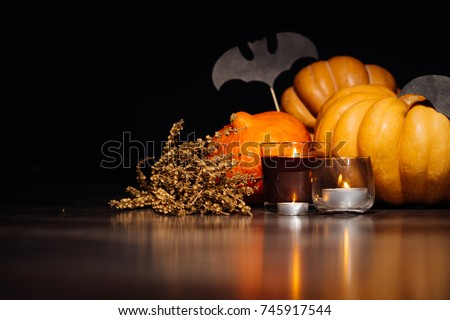 to create an atmosphere of halloween lie yellow and orange pumpkins, burning aromatic candles, lies a branch of dry grass and drawings of black bats #745917544