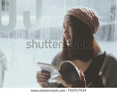 Asian woman in winter clothing drinking coffee in cafe. #745957924