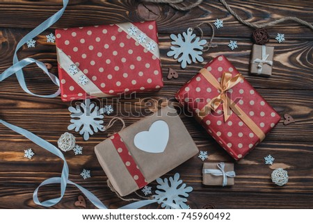 Top view shot of rustic desk with bunch of gift boxes wrapped in craft paper and various christmas decorations. #745960492