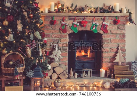 Christmas setting background, decorated Christmas tree, pine cones in the basket with fireplace on the background, candles an baubles, selective focus