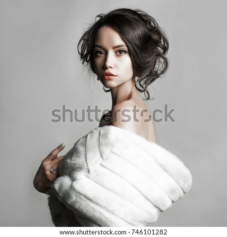 Fashion studio portrait of beautiful lady with elegant hairstyle in white fur coat. Winter beauty in luxury. Fashion fur. Beautiful woman in luxury fur coat. Fashion model posing in eco-fur coat #746101282