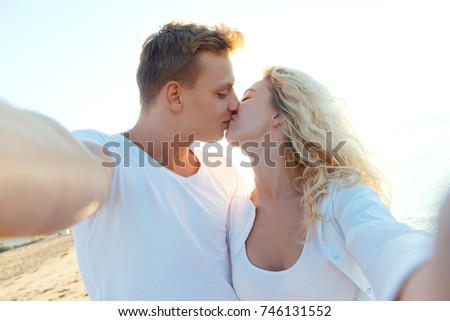 Cropped shot of a young kissing couple taking a selfie on the beach #746131552