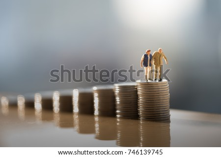 Concept of retirement planning. Miniature people: Old couple figure standing on top of coin stack. #746139745